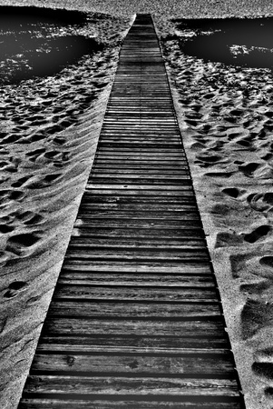 royalty free: wooden walkway onto sandy beach black and white stock photo