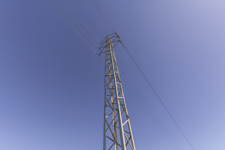megawatts: View electrical tower from below on blue sky background