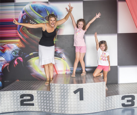 A mother and her daughters on a podium of competition