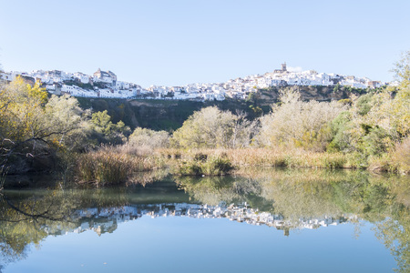 Panoramic of Arcos de la Frontera reflected in the river, white town built on a rock along Guadalete river, in the province of Cadiz, Spain