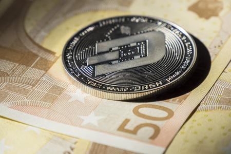 Cryptocurrency coins over euro banknotes; Dash coin