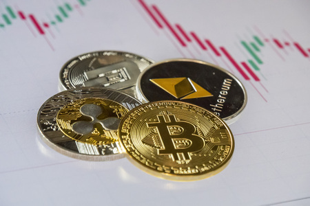 Cryptocurrency coins over trading graphic japanese candles; Bitcoin, Ethereum, Dash and Ripple coins Stock Photo