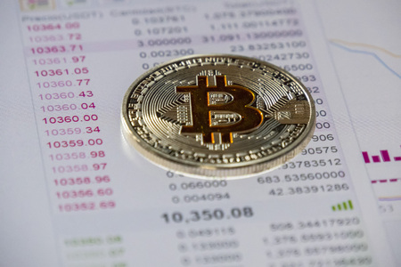 Cryptocurrency coins over buy and sell graphic; Bitcoin  coin
