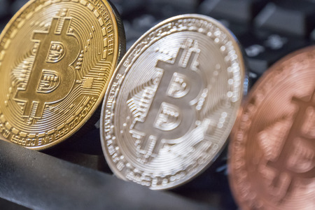 Cryptocurrency coins over black keyboard; Bitcoin  coins Stock Photo