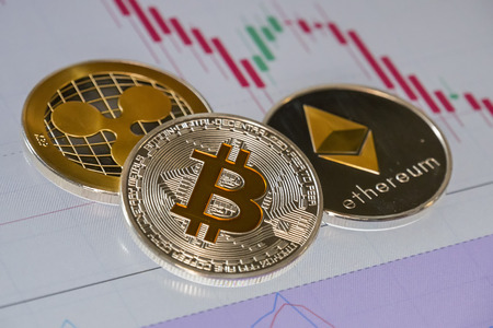 Cryptocurrency coins over trading graphic japanese candles; Bitcoin, Ethereum and Ripple coins Stock Photo