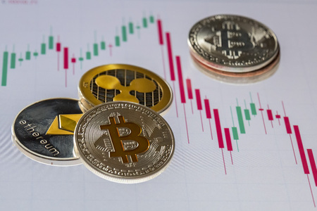 Cryptocurrency coins over trading candles graphic screen; Bitcoin, Ethereum and Ripple coins