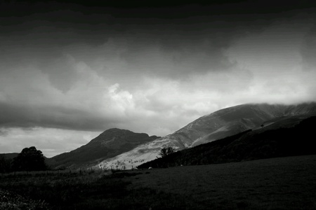 dark landscape: Dark landscape with rolling hills, stormy dark clouds with light breaking on a hillside. B&W