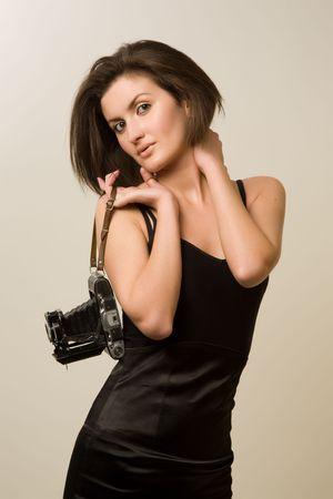 Beautiful girl holding retro camera isolated in studio photo