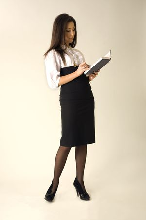 Beautiful girl in business outfit with blue notepad and pen photo