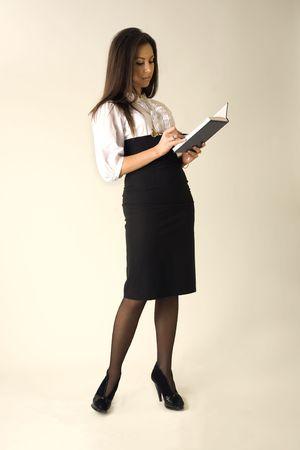 Mooi meisje in zakelijke outfit met blauwe notitieblok en pen