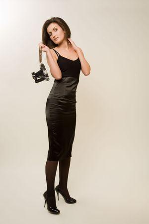 Attractive girl holding retro camera isolated in studio photo