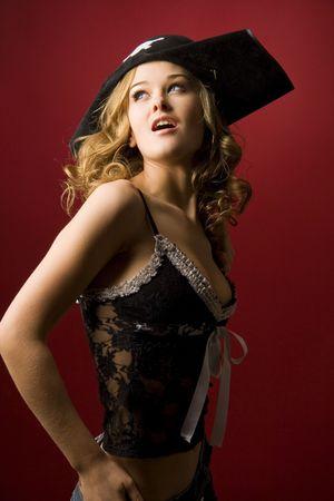 Aantrekkelijk meisje in piraat hoed met schedel geïsoleerd op rode achtergrond Stockfoto