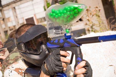Paintball-speler met pistool vol met groene verf