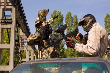 thrilling: Two paintball players on the car, outdoors