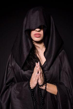 Praying nun, isolated on black background
