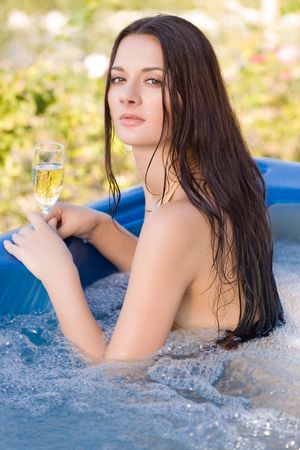 Sensual girl with champagne glass in pool photo