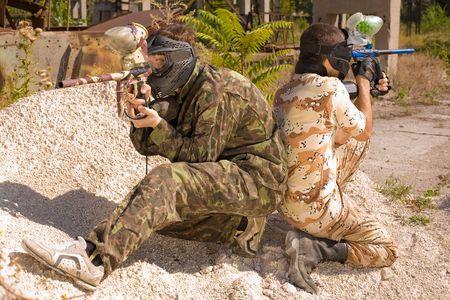 Twee paintball spelers in actie, buitenshuis Stockfoto