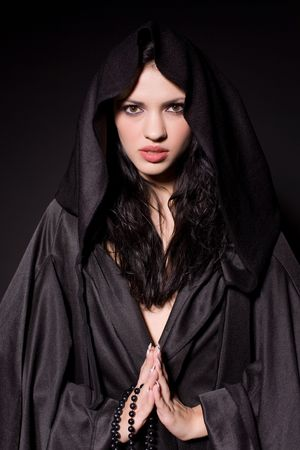 Bidden meisje in non outfit over zwarte achtergrond Stockfoto