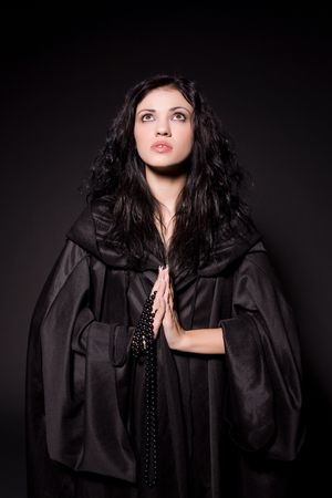 Jong meisje in biddende non outfit over zwarte achtergrond