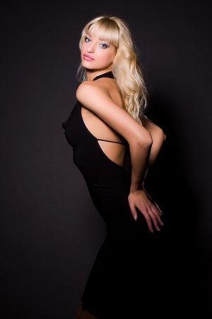Aantrekkelijk meisje in zwarte jurk, studio opname