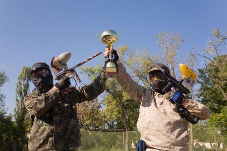 Paintball spelers met geweren en gouden beker Stockfoto