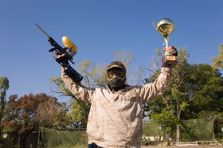 Paintball player with gun and gold cup  photo