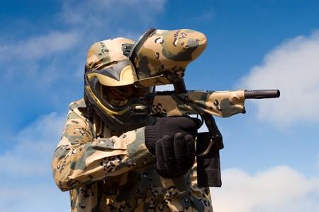 Paintball-speler met revolver over blauwe hemel achtergrond