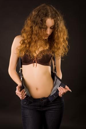 Red-haired girl undressing, studio shot over dark background   photo