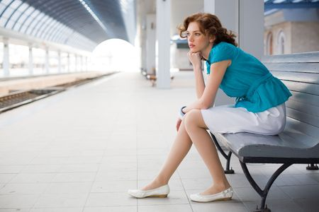 Upset girl in casual clothing on railway station