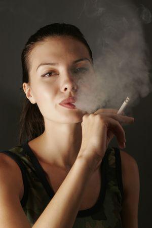 chica fumando: Sexy girl en camuflaje con cigarrillo, estudio de disparo Foto de archivo