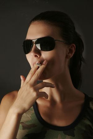 Military girl in camouflage with cigarette, studio shot  photo