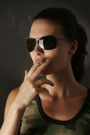camouflage woman: Sexy girl in camouflage with cigarette, studio shot  Stock Photo