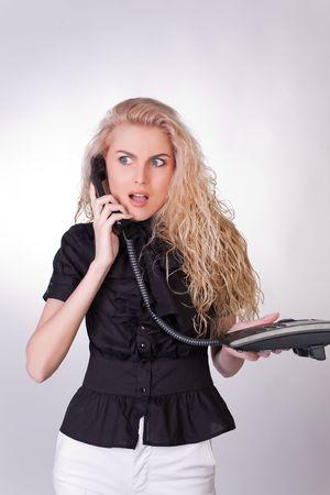 Shocked businesswoman with a phone, closeup studio shot photo