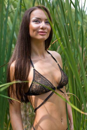 transparent dress: Girl in reed smiling, closeup shot