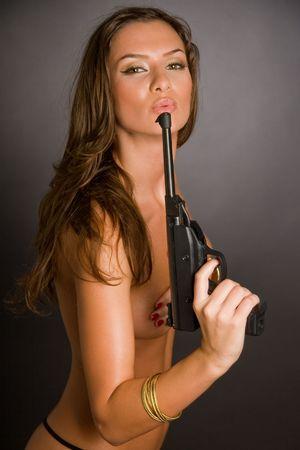 necked: Naakt meisje met pistool geïsoleerd op zwart, studio shot