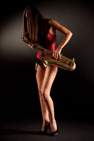red corset: Anonymous girl in red corset with sax, vertical shot Stock Photo