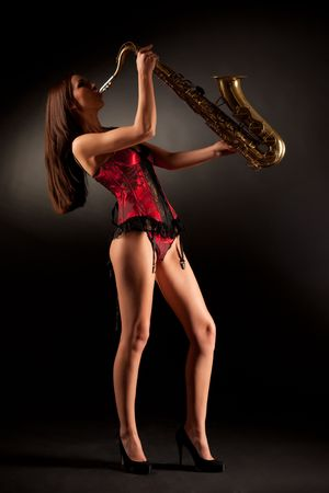 red corset: Anonymous girl in red corset playing sax, vertical shot Stock Photo
