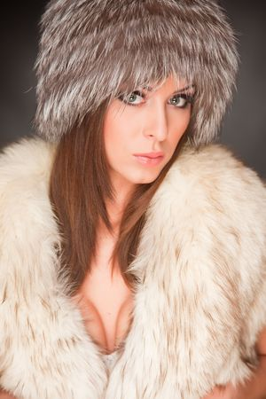 Woman with green eyes in furry hat, close up shot photo