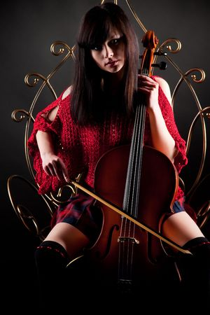 chear: Brunette girl in red with cello, studio isolated shot