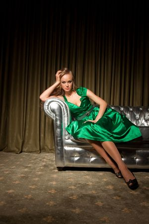 stilish: Girl in green dress sitting on couch, studio isolated shot Stock Photo