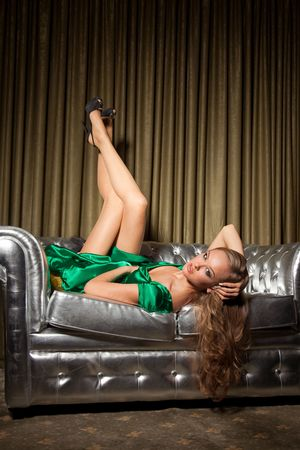 stilish: Girl in green dress laying on couch, studio isolated shot