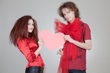 Girl and boy holding heart, studio isolated shot photo