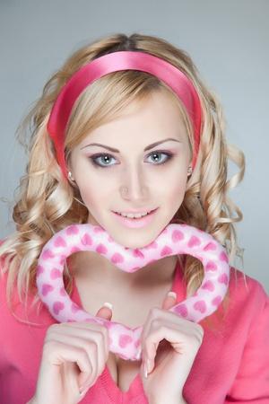 Smiling pretty glamorous girl, holding heart photo