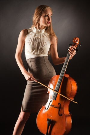 Elegant girl playing on bass-viol, studio isolated shot photo