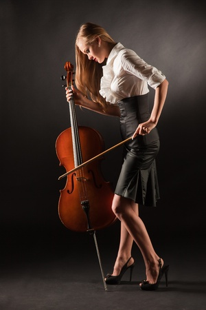 Elegant girl playing with passion on bass-viol, studio shot photo