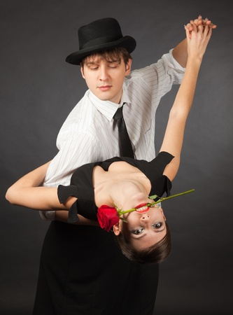 Dancing tango pair, girl holding red rose in mouth photo