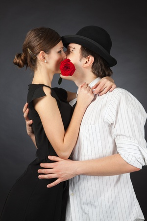 Couple kissing and holding red rose photo