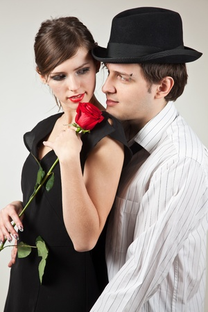 Young couple and red rose, studio isolated shot photo