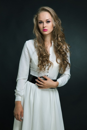 Young attractive girl in white dress, isolated over dark background photo