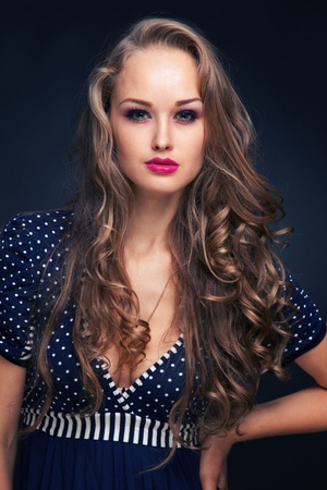 Attractive young girl in blue dress, vertical studio isolated shot